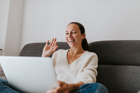 Happy woman waving hand video call on laptop at home