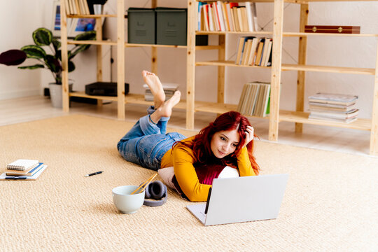 Woman with head in hands watching movie while lying on carpet at home
