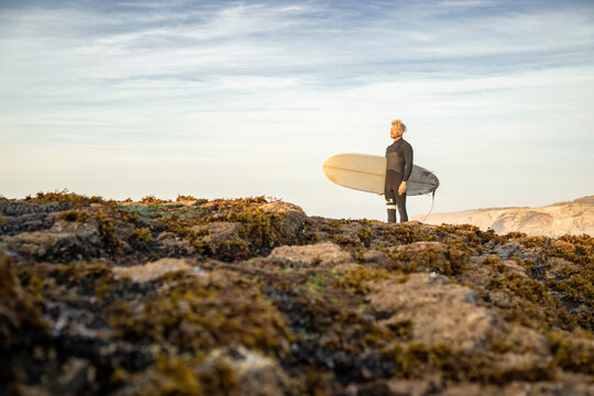 Male surfer standing with surfboard on rock formation at beach against sky