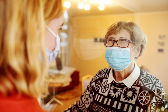 Grandmother wearing face mask looking at granddaughter while standing by glass at home during Covid-19