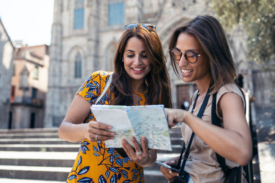 Smiling friend holding map while standing against Barcelona Cathedral Square in Barcelona, Catalonia, Spain