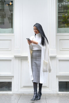Smiling businesswoman using mobile phone against white wall
