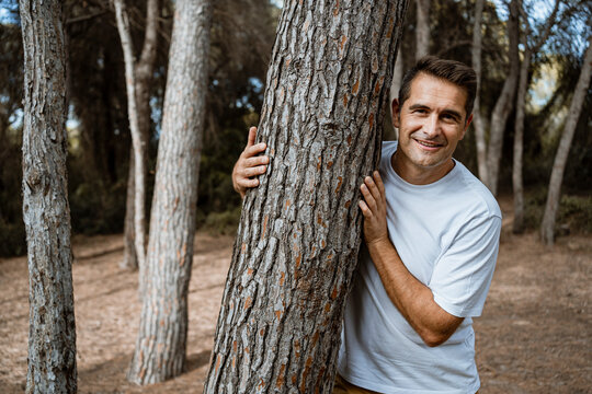 Smiling man embracing tree trunk in forest during vacation