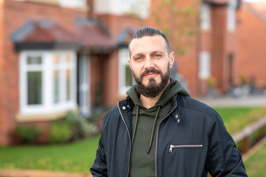 Confident bearded man standing outside new home