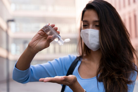 Businesswoman in face mask pouring sanitizer on hand during COVID-19