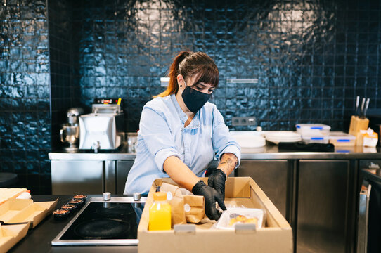 Female chef wearing face mask while keeping take out food in cardboard box at restaurant kitchen counter
