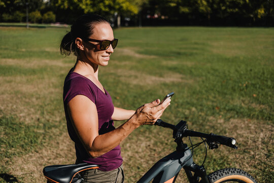 Smiling female athlete using mobile phone while standing with electric mountain bike at park