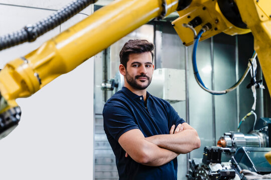 Confident male worker with arms crossed standing in factory
