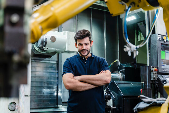 Male manual worker with arms crossed smiling while standing in factory