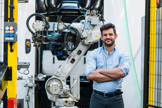 Smiling male entrepreneur with arms crossed standing against robotic arm at industry