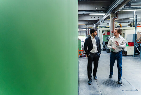Male entrepreneur with hands in pockets listening to manager walking in manufacturing factory