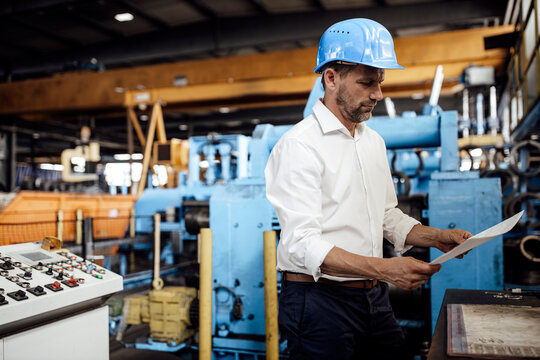 Male entrepreneur reading document while standing in factory