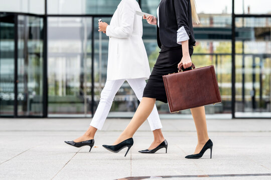 Businesswoman with briefcase using mobile phone while walking by colleague on footpath