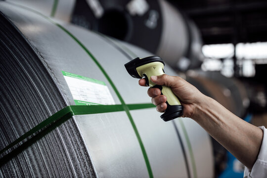 Man's hand scanning barcode on steel rolls in industry