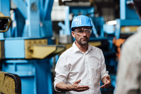 Businessman wearing protective eyewear discussing with unrecognizable person at industry