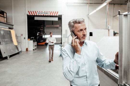 Businessman talking on mobile phone while colleague walking on background at industry