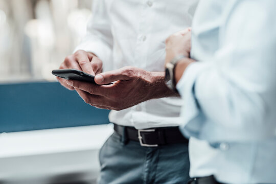 Businessman using smart phone while standing by male colleague in industry