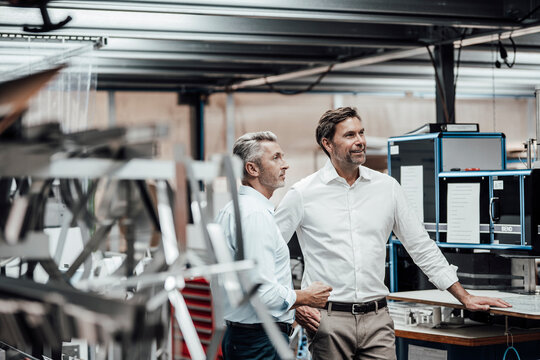 Mature colleague discussing with smiling manager while standing by manufacturing machinery in factory