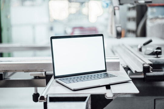 Laptop with blank screen on machinery in factory