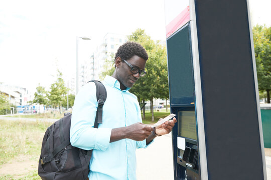 Male professional looking at bicycle sharing receipt by ticket machine in city