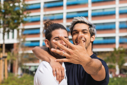 Smiling man showing engagement ring while standing by gay partner in park