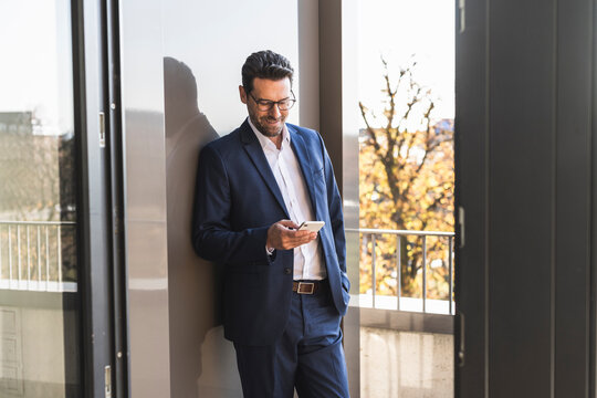 Male entrepreneur using mobile phone while standing with hand in pocket by balcony at office