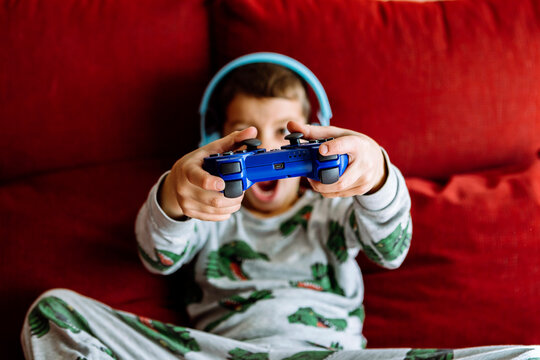Boy wearing headphones while showing video game on sofa at home