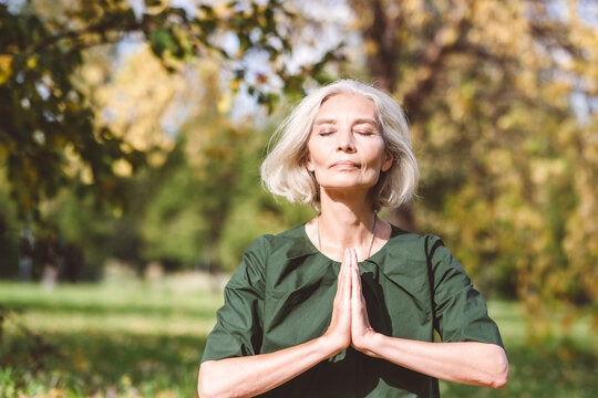 Mature woman sitting with hands clasped while doing yoga at park