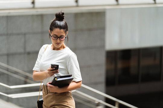 Beautiful young female entrepreneur using smart phone in city