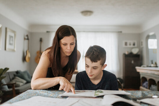 Mother teaching son on table at home during curfew