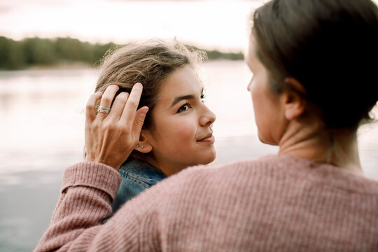 Smiling daughter looking at caring mother by lake