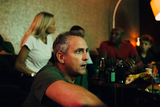 Shocked mature man watching sports while family and friends talking in background at home