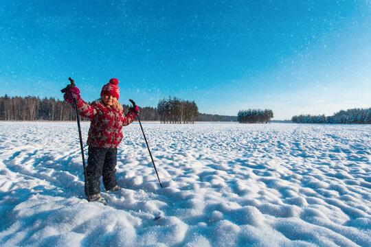 happy cute girl ski in winter nature, kids seasonal sport