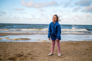 Dziewczynka w niebieskiej kurtce stojąca na plaży nad morzem