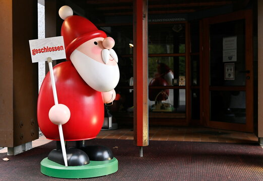"""A wooden Santa Claus figure holding a sign """"closed"""" is seen in Seiffen"""