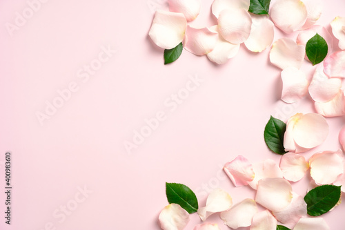 Frame border of rose petals and leaves on a pink background. Flat lay, top view. Greeting card layout for Valentine's Day, Mother's Day, Anniversaries