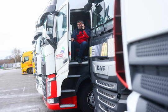 A man makes a phone call from inside his lorry at Ashford International Truck Stop