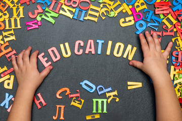 Child's hand laid out the word education from multicolored plastic letters