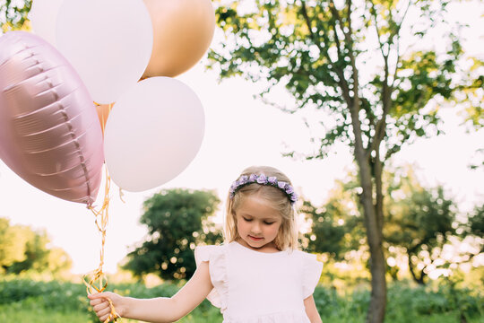 Small shiny girl with pink balloons in the garden