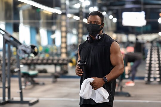 Black bodybuilder in face mask holding water, towel at gym