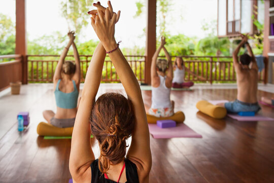 Back view of young people group practicing yoga with instructor. Stretching class at summer retreat camp to keep fit and health. Woman fitness, recreational sport activity on family holiday.