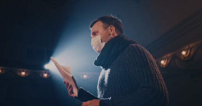 Actor in mask rehearsing play in theater
