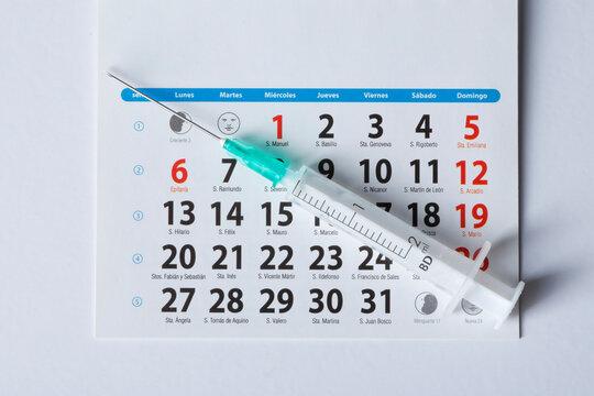 Coronavirus vaccine calendar with syringe on white background