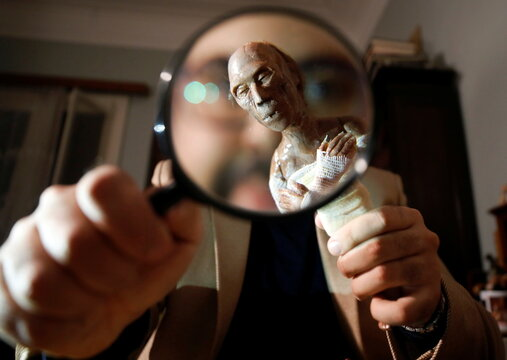 Journalist and artist Fadi Francis holds a magnifying glass and a white ceramic paste character of the mummy of ancient Egyptian King Ramses II, in Cairo
