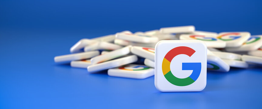 Logos of the company Google / Alphabet on a heap. One tile standing upright in front. Web banner size with copy space - Selective focus