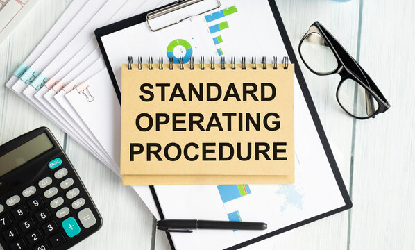 Standard Operating Procedure text on paper in open diary with spectacles, colourful push pin, pen and calculator on the wooden table - business and finance concept