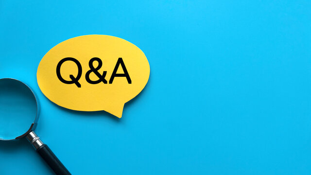 Top view of magnifying glass and yellow speech bubble written with Q&A Question and Answer on blue background with copy space.