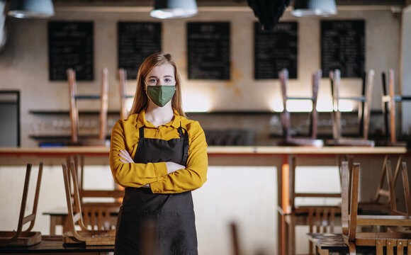 Frustrated waitress standing in closed cafe, small business lockdown due to coronavirus.