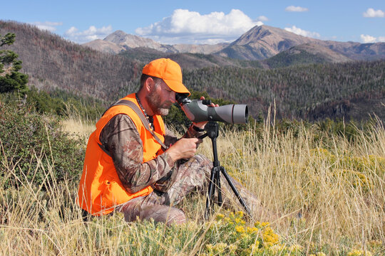 adult deer hunter looking through spotting scope in mountains