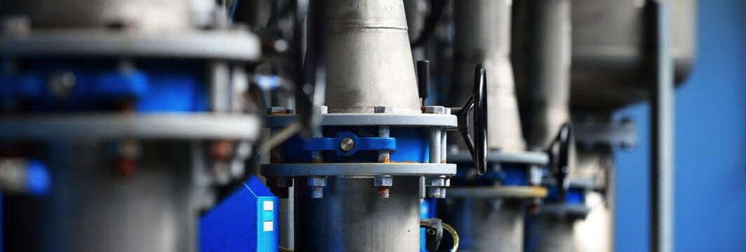Large industrial water treatment and boiler room. Piping, flanges, butterlfy valves, rusty and corroded bolts. Industry, technology, special equipment, chemistry, heating, work safety. Panoramic view